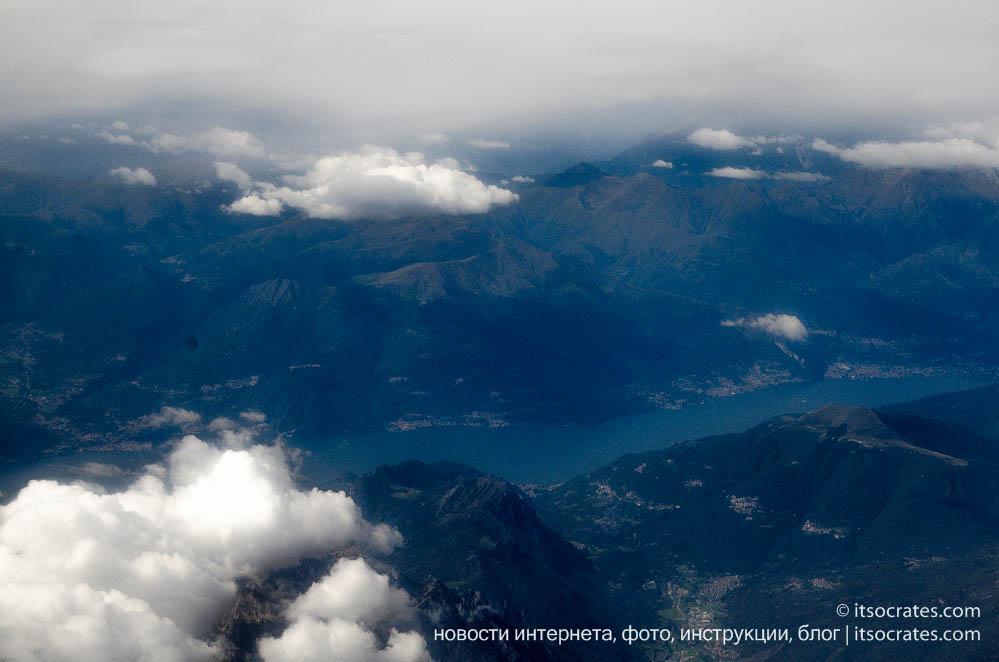 Вид из иллюминатора на горы, первый признак Италии когда летишь из Мюнхена, Германия