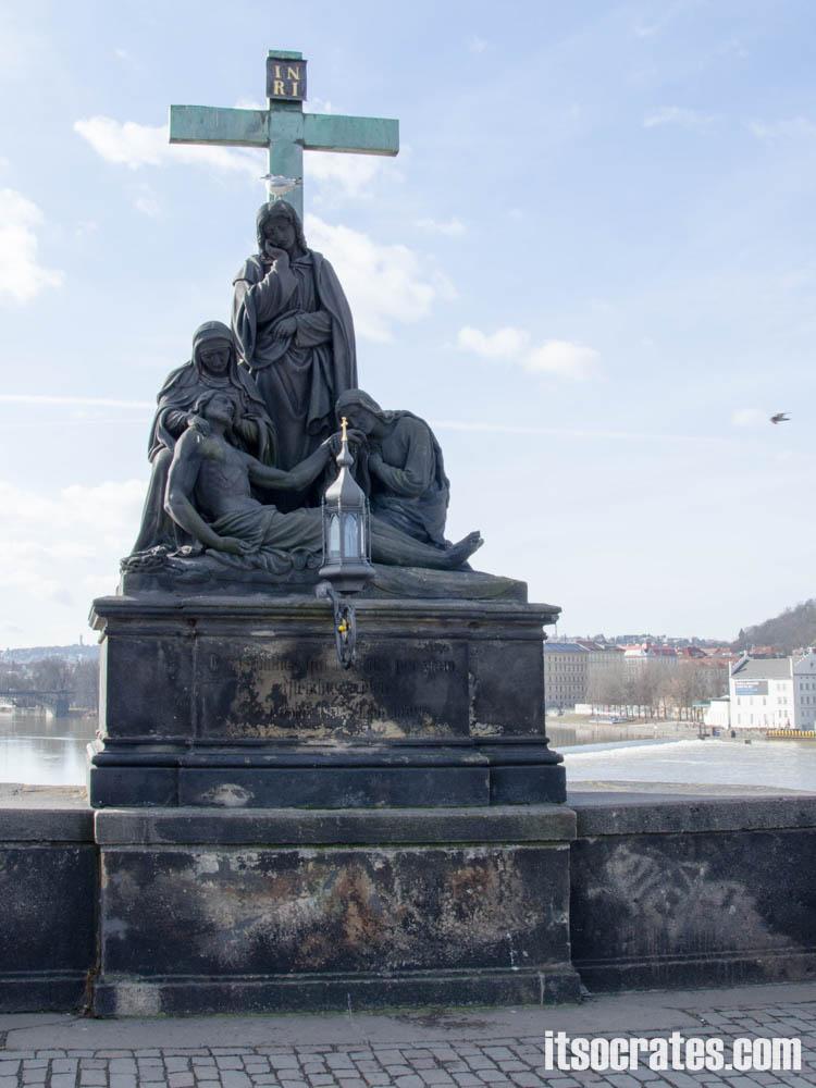 Карлов мост в Праге, Чехия - статуи на мосту - Пьета; Э.Макс, 1869 г. — В XIX веке в этом месте наказывали осужденных, связав им руки и ноги, их сбрасывали с моста во Влтаву, выживших объявляли невиновными и освобождали