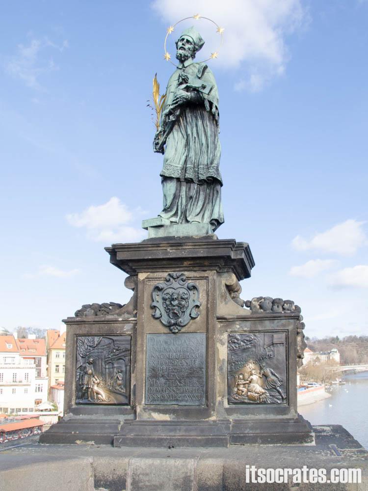 Карлов мост в Праге, Чехия - статуи на мосту - Св. Ян Непомуцкий; Й.Брокофф, 1683 г. — Самый популярный Святой в Богемии был священником и проповедником при дворе короля Венцеслава; король посадил Яна Непомуцкого в тюрьму и, сбросив с Карла моста, утопил во Влтаве